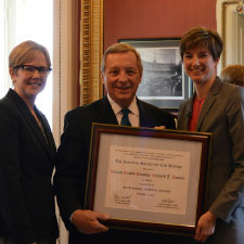 Connie Lee (left) and Erika Shugart (right) present the ASCB Public Service Award to Sen. Richard Durbin.
