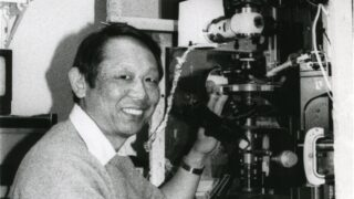 Black and white photograph of Shinya Inoue in his laboratory with one of his microscopes.