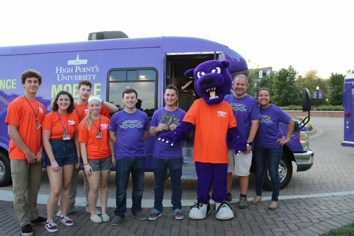 Faculty and undergraduate volunteers (from left to right: Nathan Grinalds, Kendall Ziegler, Austin Kratz, Bella Grifasi, Mike Rizzo, Jackson Sparks, Prowler the Panther, Neil Coffield and Verónica Segarra) in front of the HPU Mobile Lab (before COVID-19).